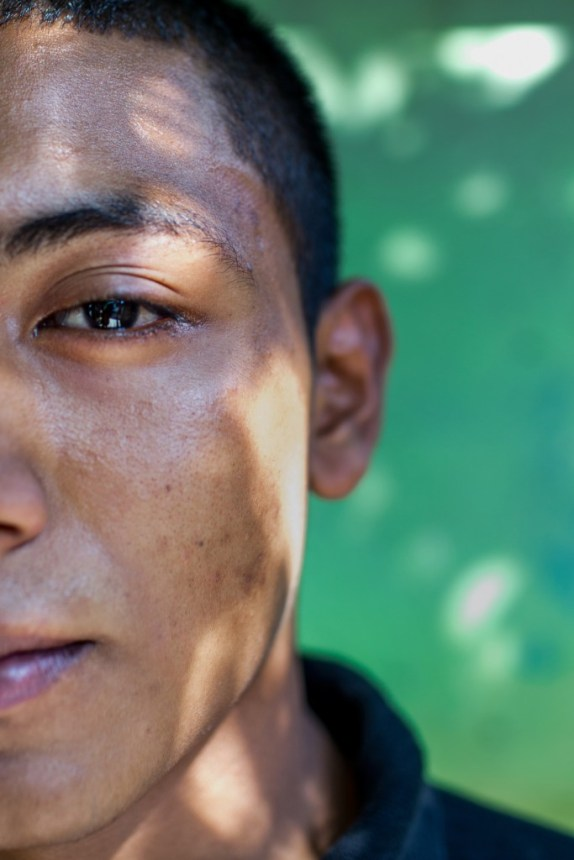 """April 2017, El Salvador, San Salvador. """"Demon"""" was unsure about showing his whole face or not. He wanted to but he was nervous. A young rapper who teaches youth in his neighborhood with the approval of Barrio 18 which controls it, many members of his family are gang involved, but he wants to do music. A few days after this image was taken he was arrested and imprisoned accused of killing a police officer. 3 months later he has been acquitted but still fears the police will seek retribution because they believe he is guilty. He has witnessed 2 friends killed in front of him. One by enemy gangs and one by the police. (Natalie Keyssar)"""