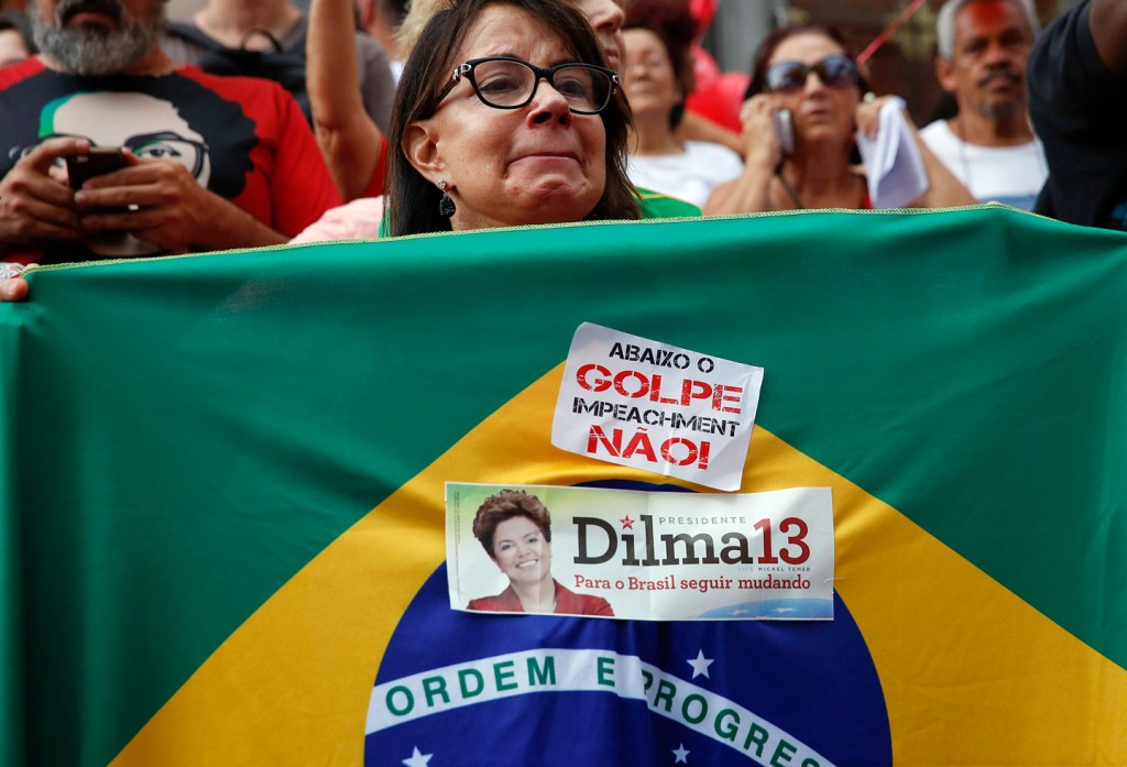 A demonstrator holds a Brazilian flag with a sticker that reads in Portuguese