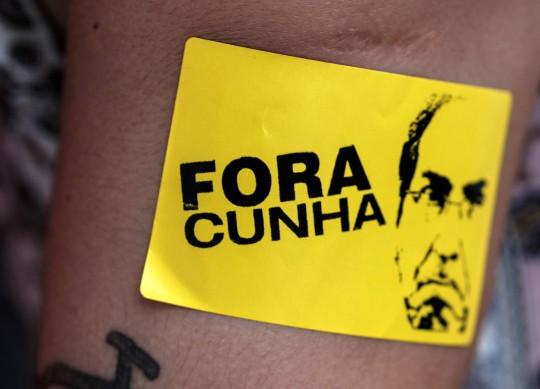 A supporter of Brazilian President Dilma Rousseff demonstrates against her possible impeachment with a sticker reading