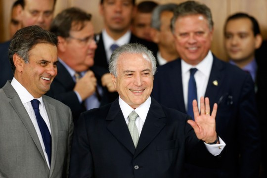 BRASILIA, BRAZIL - MAY 12: Brazil's interim President Michel Temer (R) waves with Senator Aecio Neves (L) at a signing ceremony for new government ministers at the Planalto presidential palace after the Senate voted to accept impeachment charges against suspended President Dilma Rousseff on May 12, 2016 in Brasilia, Brazil. Rousseff has been suspended from her presidential duties and will face a Senate trial for alleged manipulation of government accounts. (Photo by Igo Estrela/Getty Images)