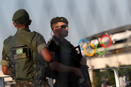 Brazilian security forces stand guard outside the Maracana stadium in Rio de Janeiro on August 5, 2016, ahead of the opening ceremony of the Rio 2016 Olympic Games. A vast security blanket of 85,000 military personnel and police -- twice the number on duty at the 2012 London Games -- are draped over the city to ward off the threat of street crime and terror attacks. / AFP / Adrian DENNIS (Photo credit should read ADRIAN DENNIS/AFP/Getty Images)