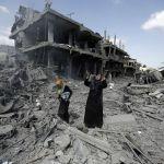 A Palestinian woman pauses amid destroyed buildings in the northern district of Beit Hanun in the Gaza Strip during an humanitarian truce on July 26, 2014. Os corpos de pelo menos 35 palestinos foram retirados dos escombros de Gaza durante uma trégua, elevando o total de vítimas do ataque israelense desde 8 de julho a 900, de acordo com médicos. AFP PHOTO / MOHAMMED ABED (Photo credit should read MOHAMMED ABED/AFP/Getty Images)