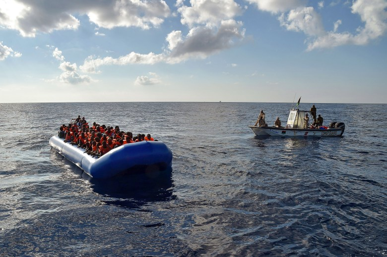 "TOPSHOT - Migrants and refugees sit on a rubber boat as the Libyan coastguards patrol, during a rescue operation of the Topaz Responder, a rescue ship run by Maltese NGO ""Moas"" and the Italian Red Cross, on November 4, 2016 off th Libyan coast.Around 750 migrants were rescued across the Mediterranean Thursday by the Italian coast guard, a Frontex ship, a Save The Children vessel, German NGO Jugend Rettet's Iuventa and two boats run by the Malta-based MOAS (Migrant Offshore Aid Station). But at least 110 migrants are feared drowned after they were forced at gunpoint to set sail from Libya, while many more may have died in a separate shipwreck, survivors said. / AFP / ANDREAS SOLARO (Photo credit should read ANDREAS SOLARO/AFP/Getty Images)"