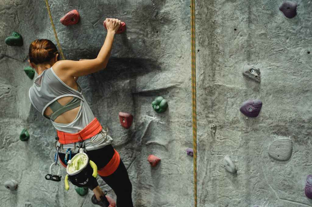 unrecognizable climber ascending artificial rock with holds