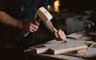 crop woodworker making patterns on wooden board