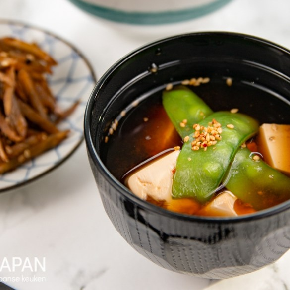 Foto van rode miso soep met tofu, sugarsnaps, en shichimi togarashi kruiden mix.