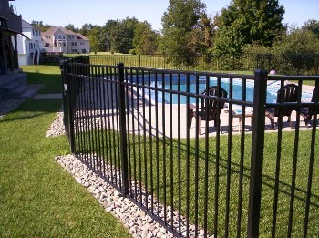 An OnGuard Starling 54 inch, 3 rail in black. Note the area without stone - there is a straight top gate there that blends with the top rail. Straight top gates are often used at the rear or side of the enclosure for access to mowers or other yard maintenance machinery. Many times a 3 foot wide straight top is placed close to the filter to get to it without walking all the way around from the main entry.
