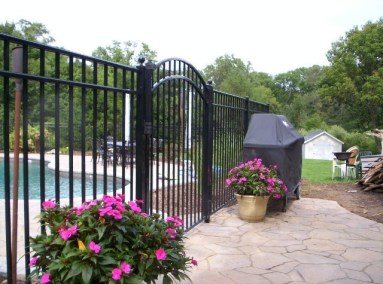 Black is timeless. Black is also the undisputed favorite color for pool fence. You can see here that it blends well with the pavement and the arched top gate with ball caps on the posts make this one beautiful entry. OnGuard offers sveveral enhancements for the Starling style that can add even more appeal to your pool enclosure.