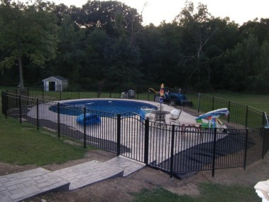 Siskin Style BOCA code compliant pool fence in Black. Here the sections are angled to conform to the pool deck. An angle of about 10 degrees is possble without modifying the rail openings on the post. A little work may be desireable on the inside notch of the rail so that both sides of the rail notch sit flush on the post. OnGuard offers horizontal, vertical, and universal swivels as well as wall mount brackets.