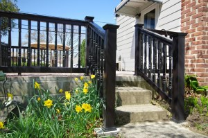 A Grand Illusions vinyl deck railing with a 'T' top and Colonial balusters in black.