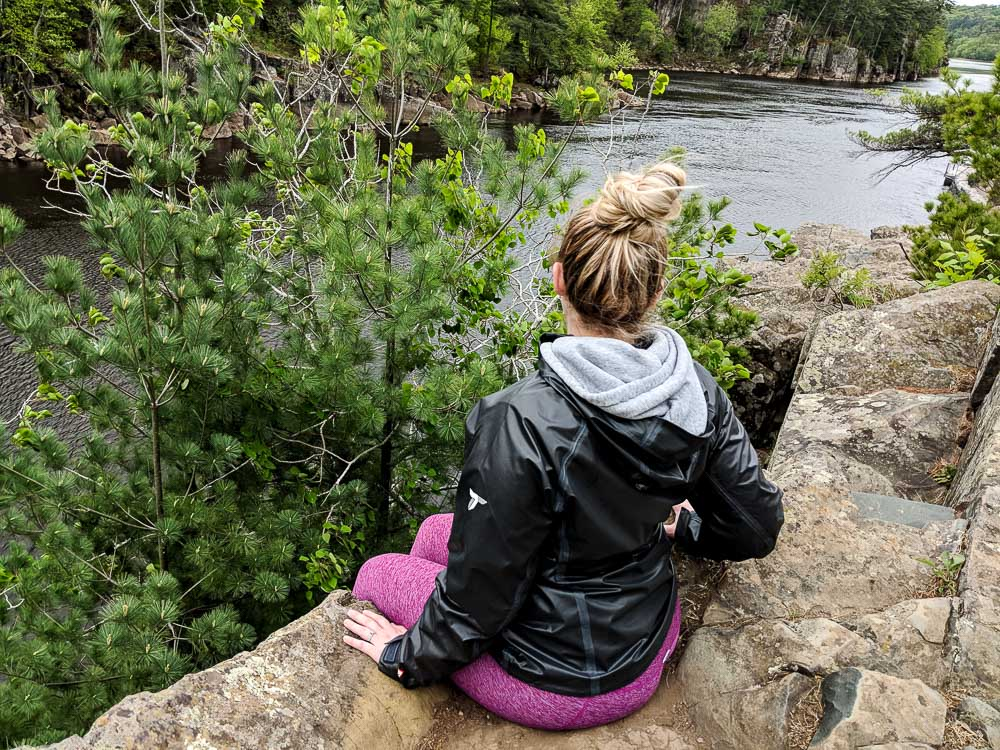 woman sitting on edge of cliff
