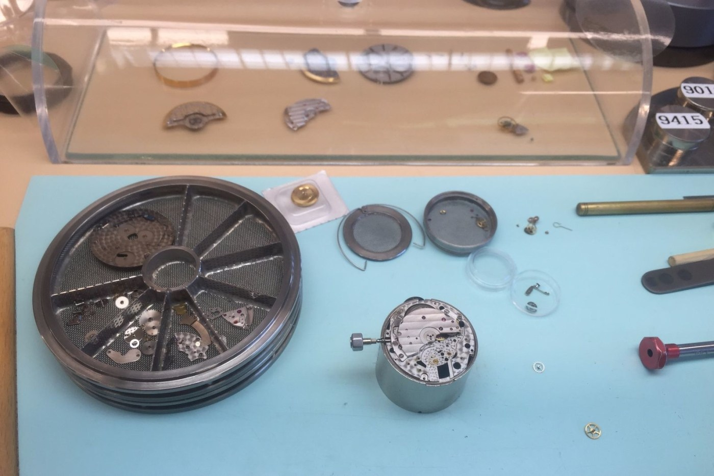The movement is disassembled to the main plate and parts are put into a carriage for cleaning