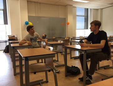 Foto van Branco en Alex in een lege klas lokaal