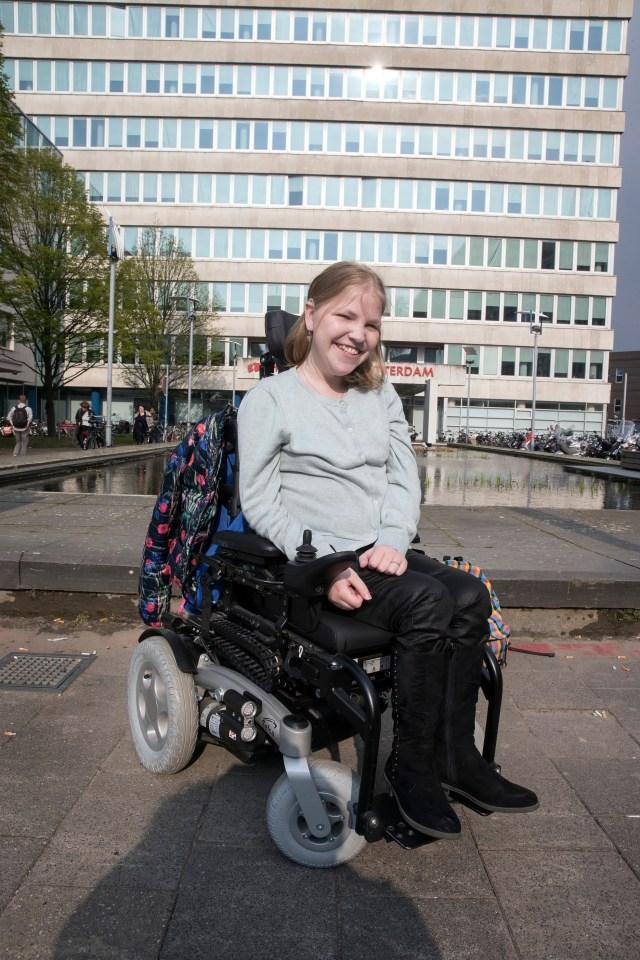 Vivian van Leeuwen in rolstoel voor gebouw hogeschool