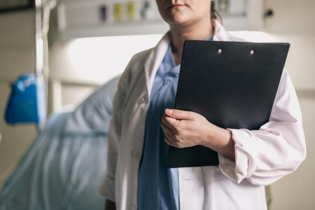 5491247b-female-medical-professional-holds-clipboard-in-hospital-room