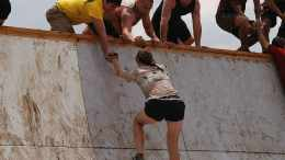 woman being helped to climb an assault course