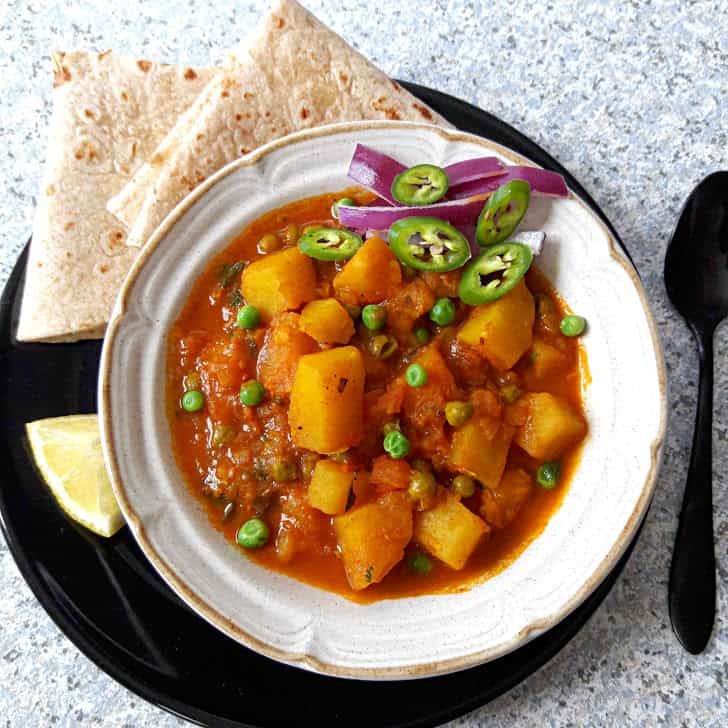 Potato and Peas Curry-Aloo Matar with Roti and onions and lemon wedge