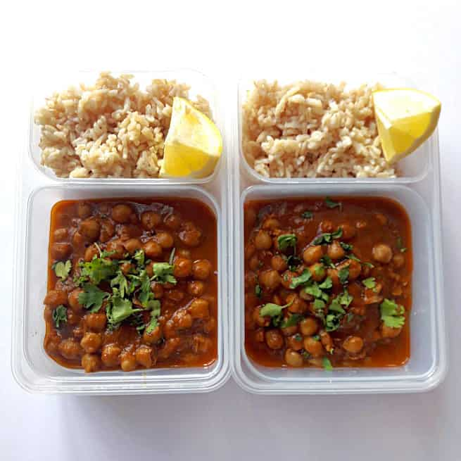 Chole with brown rice in two lunch containers with lemon wedges