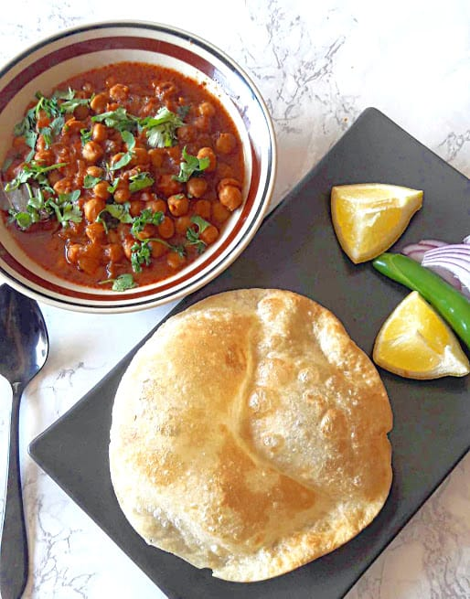 Chole and Bhature on black plate with lemon wedges and onion and chili