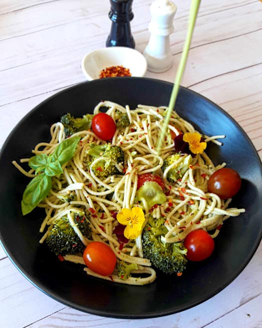 camera shot of Cashew Lemon Basil dressing getting poured over spaghetti and veggies . This delicious dinner recipe is by ProfusionCurry