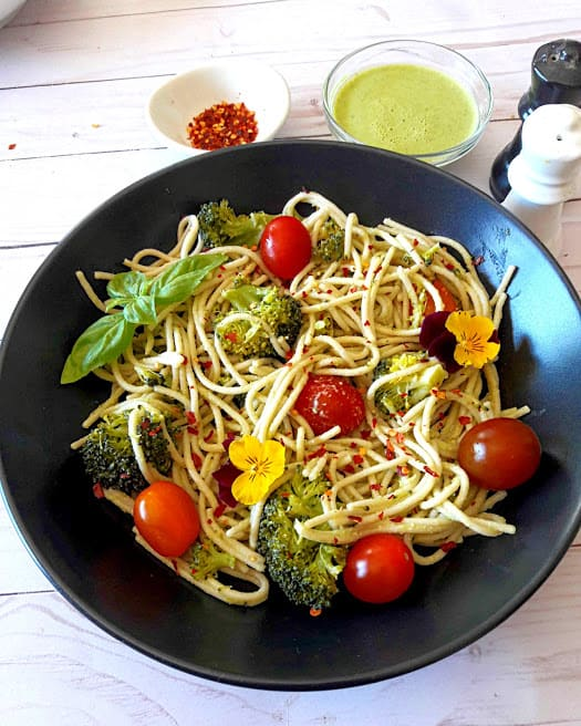Spaghetti with broccoli and cherry tomatoes with fresh basil, chili flakes on black serving plate with creamy lemon dressing on the side. A delicious ProfusionCurry recipe