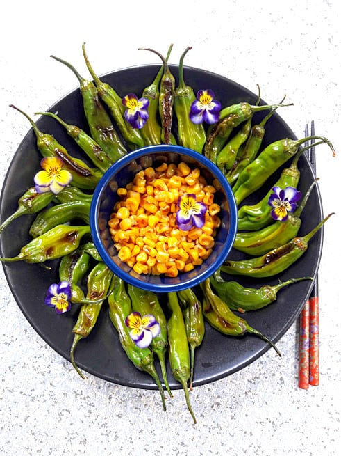 Grilled Shishito peppers served on black platter with grilled corn in the center with viola flowers spirinkle is recipe from profusioncurry
