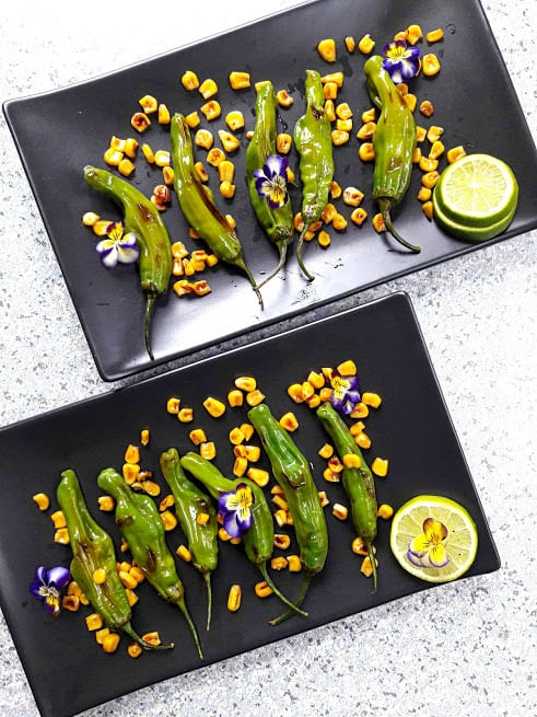 Grilled Shishito peppers and corn served on two black serving plates with lemon wedges viola flowers. This beautiful creation from Profusioncurry is ideal crowd pleaser.
