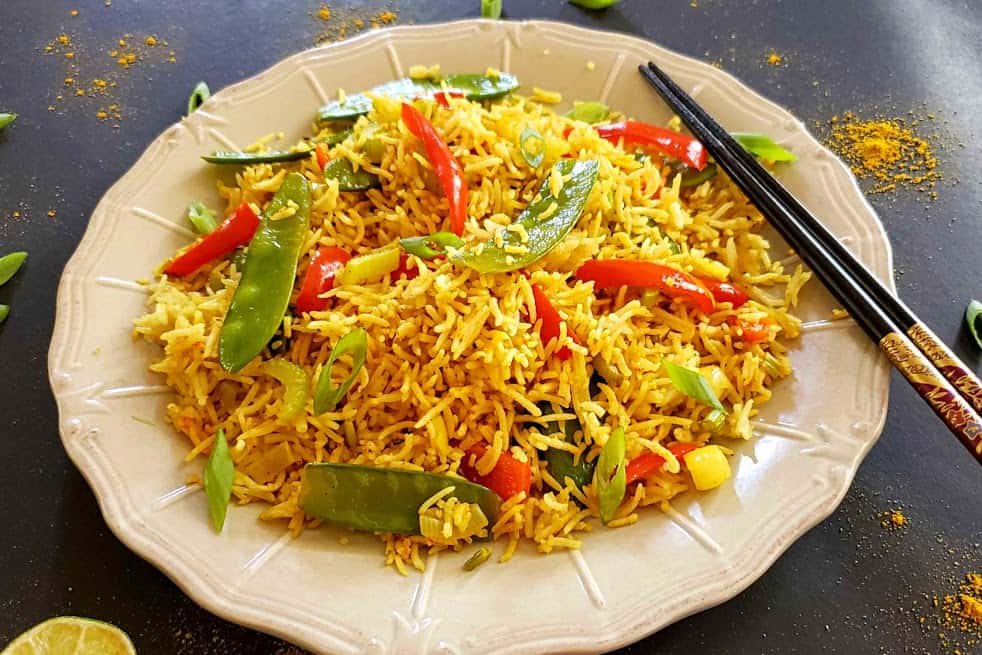 Close up shot of Curry Fried Rice with snow peas and red peppers