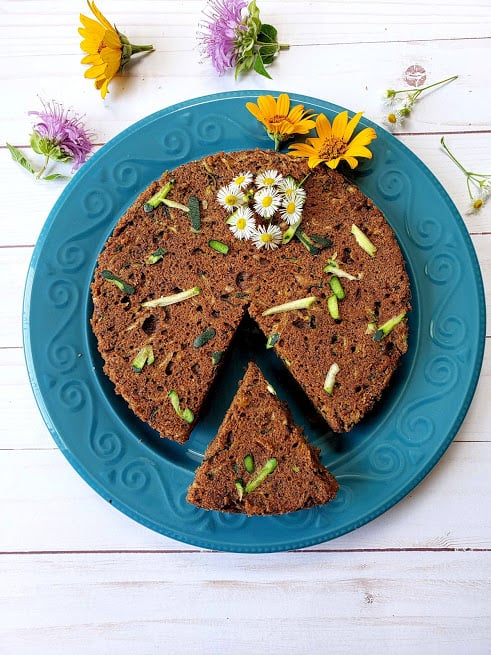 Instant Pot Zucchini Bread with cut slice served in blue plate and decorated with summer time wild flowers