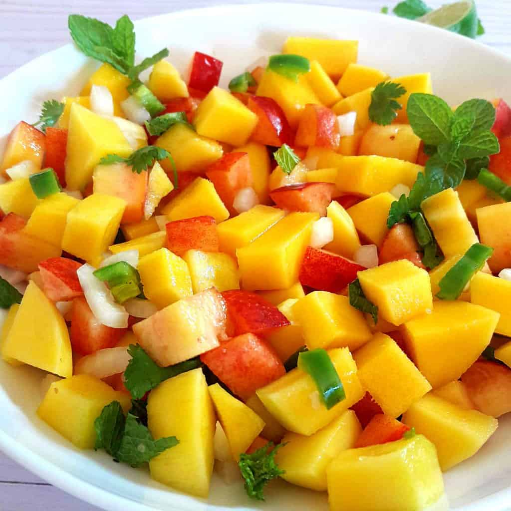 Bright yellow mangoes and peach salsa with splash of lime juice and hints of jalapeno peppers and cilantro served in white bowl