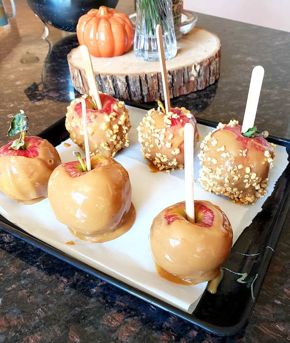 Apples dipped in Dule de leche and coated with crushed peanuts. This decadent dessert is ideal for fall parties.