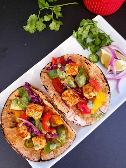 Paneer and vegetable tacos served on white platter with red onions, cilatro and lime wedges. This indian mexican fusion recipe is profusioncurry creation.