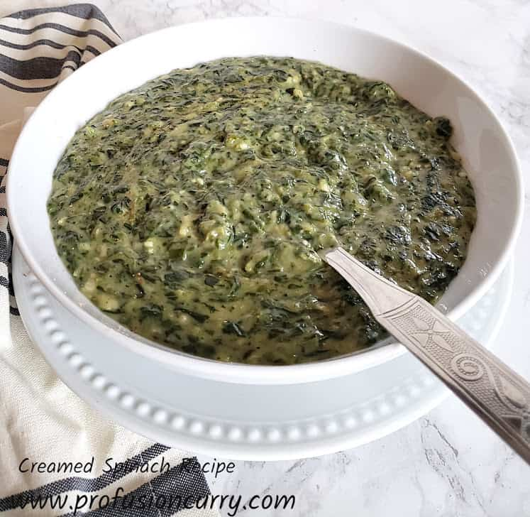 Creamed Spinach served in white serving bowl with serving spoon and kitchen towel on the side.
