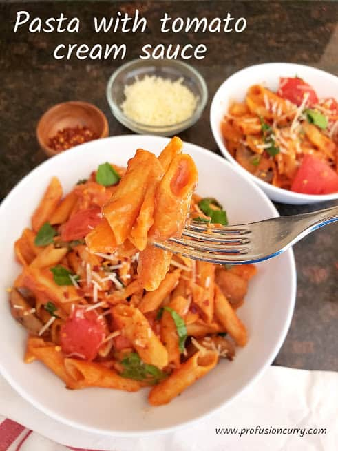 A fork hoding pasta showing velvety creamy texture of tomato cream sauce.