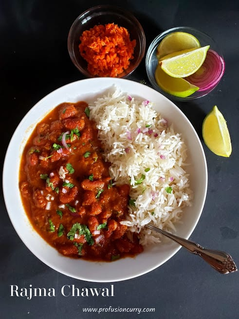 a white serving plate with red beans curry and rice which is garnished with chopped red onions and cilantro leaves. There is carrot pickle and lemon wedges on the side. This comforting Indian meal is called Rajma Chawal or Red Beans and rice.