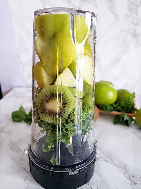 A blender jar upside down filled with raw green smoothie ingredients.