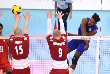 Cuba's Gutierrez spikes against Poland's Jakub Ziobrowski and Norbert Huber block.