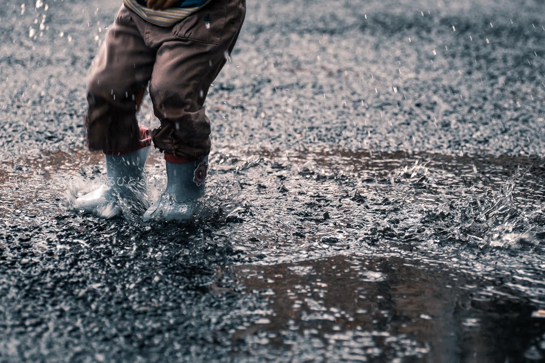 水たまりへ長靴をはいた子供が着地した瞬間