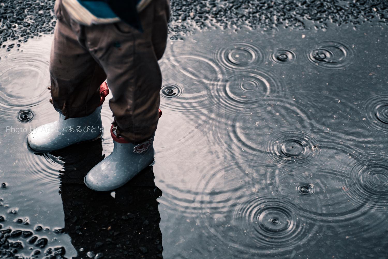 水たまりの上に立つ長靴をはいた子供と雨が降って出来た水紋