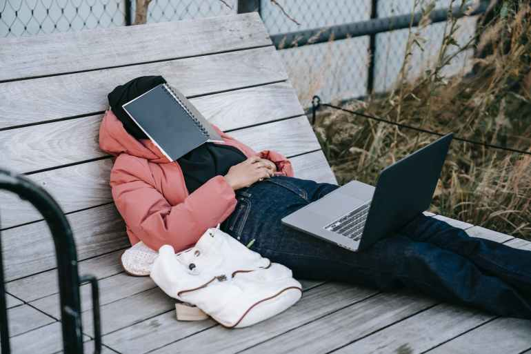 unrecognizable woman with laptop resting on bench in park