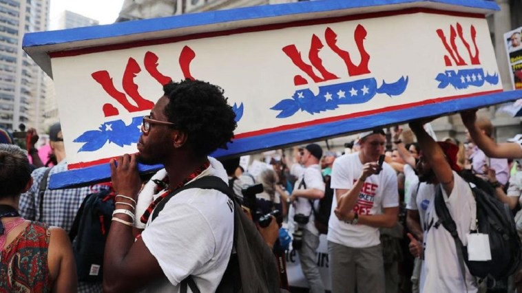 Black Lives Matter protesters hold a coffin with an upside down Democratic donkey