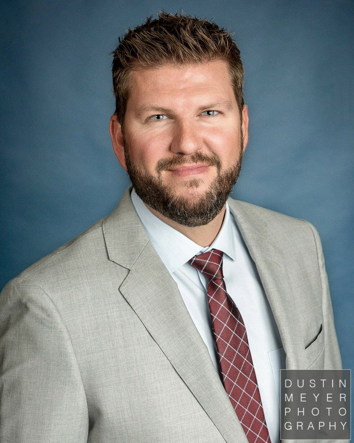 professional headshot tips male guy wearing a suit and tie with a blue backdrop for a business headshot