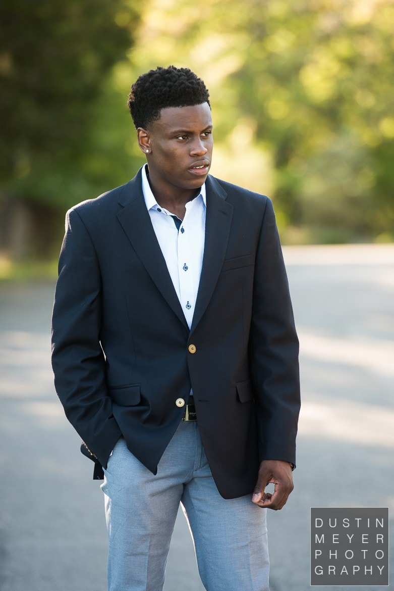 a black male model wearing jeans and a suit jacket outdoors