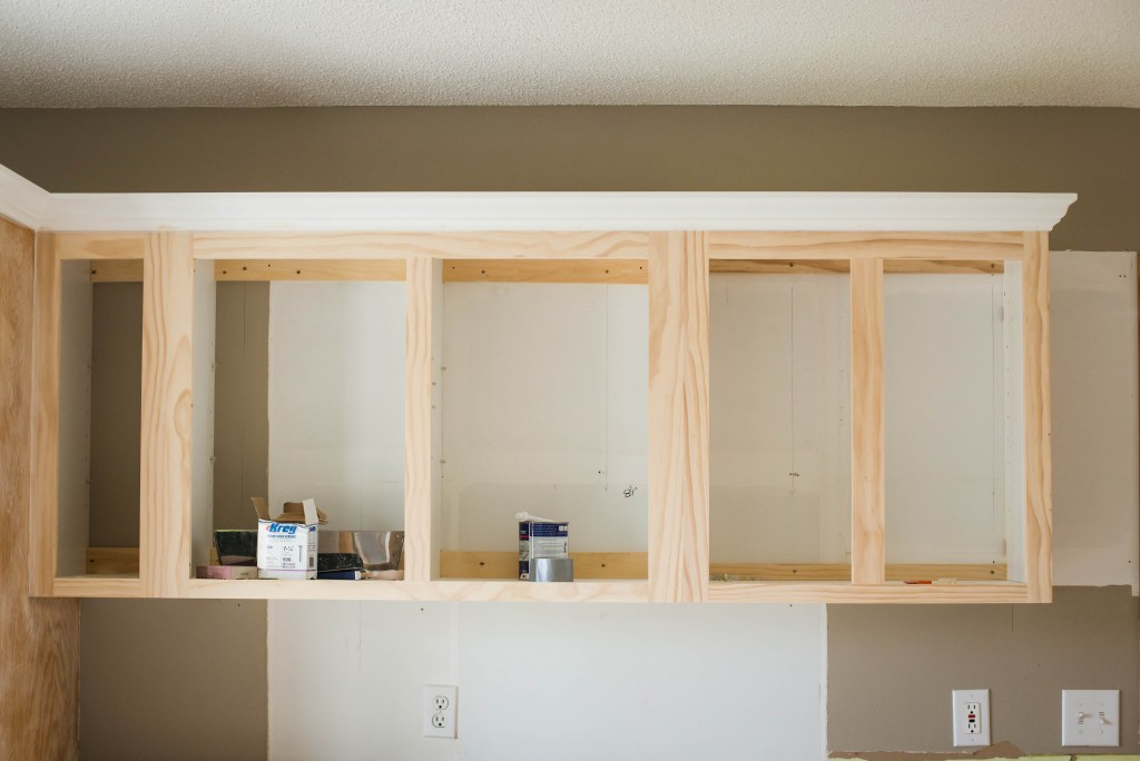 in progress photo of cabinetry being reconstructed and crown molding on top