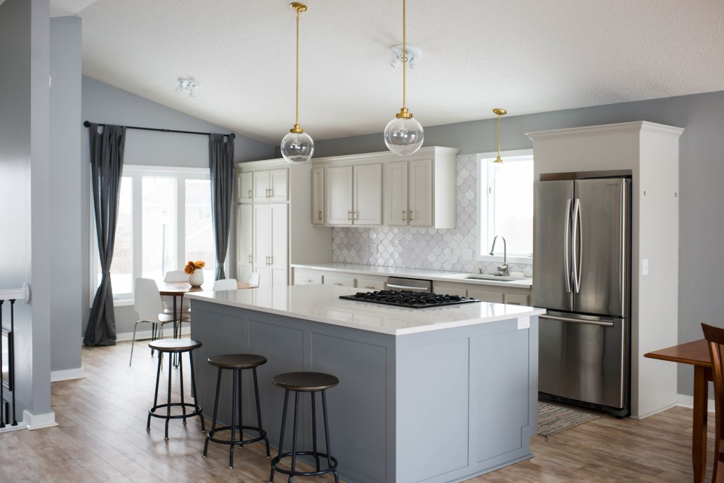 open kitchen with globe pendant lights and large open island with fish scale backplash