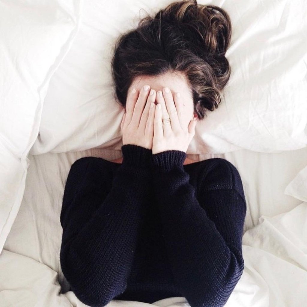 Blogger Kate Arends in bed with hands over her face.
