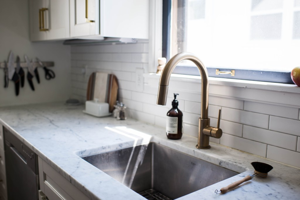 After shot of sink and final kitchen with brass gold faucet and white countertops and subway tile horizontal backsplash