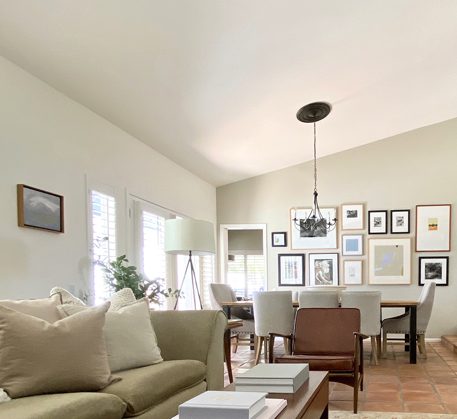The open dining room features a gallery wall and custom wood dining room table.