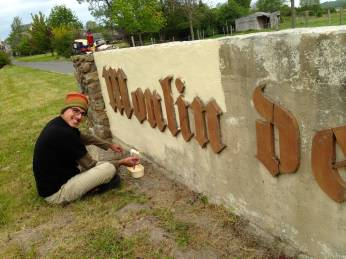 Painting the sign for the mill
