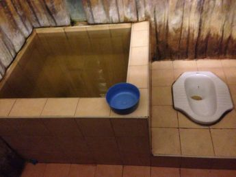 Squatting toilet with water basin used to flush